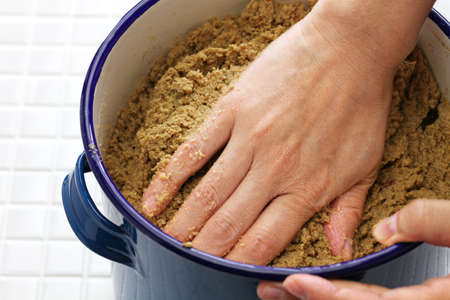 close up: maintenance of nukadoko (salted rice bran bed for pickles), japanese traditional food cooking Stock Photo