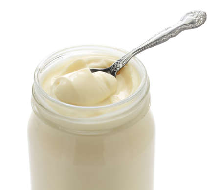 opened mayonnaise jar and spoon isolated on white background