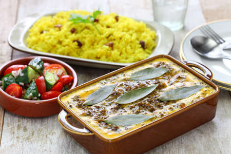 bobotie and yellow rice, south african cuisine. bobotie is a curry flavored meatloaf with baked egg on top. Stock Photo