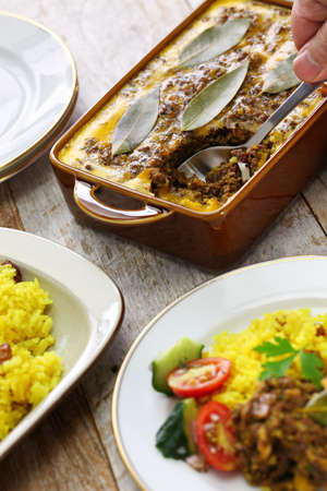 meatloaf: bobotie and yellow rice, south african cuisine. bobotie is a curry flavored meatloaf with baked egg on top. Stock Photo