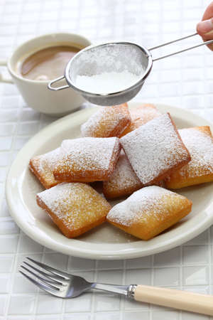 homemade new orleans beignet donuts, sprinkle powdered sugar with sieve Stock Photo