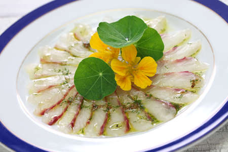 fish carpaccio, thinly sliced raw sea bream appetizer, italian dish Stock Photo