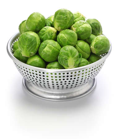 fresh brussels sprouts in colander isolated on white background Stock Photo