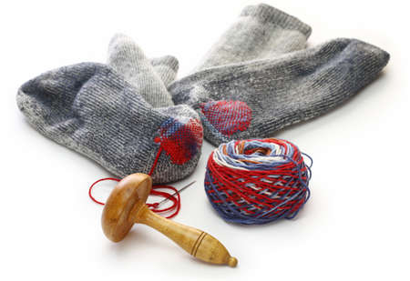darning socks, repairing holes in socks on white background