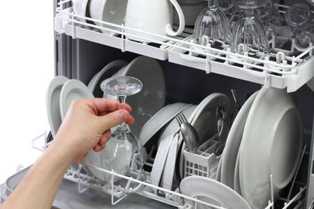 dishwasher, open and loaded with dishes, man hand taking out clean wine glass, after washing