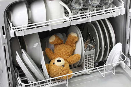 Wrong usage of dishwasher, teddy bear should never put in the dishwasher Stock Photo