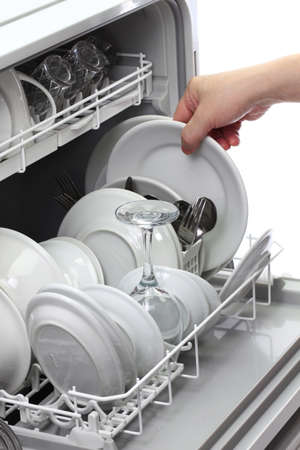 open dishwasher, man hand taking out clean dish, after washing Stock Photo