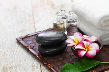 Tropical spa resort; plumeria, hot stones, towels, and massage oils Stok Fotoğraf