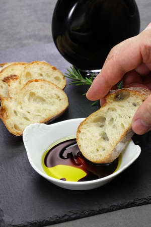 dipping baguette into balsamic vinegar and olive oil sauce Archivio Fotografico