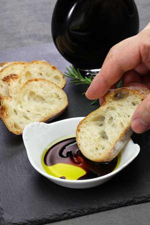 dipping baguette into balsamic vinegar and olive oil sauce 版權商用圖片