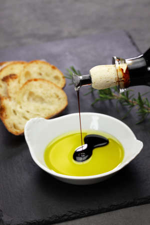 pouring balsamic vinegar into olive oil, making dipping sauce Stock fotó