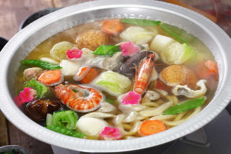 Japanese cuisine, udon suki, hot pot with udon noodles and fresh vegetables and seafood 스톡 콘텐츠