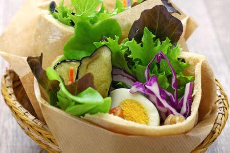 sabich: israeli pita sandwich with fried eggplant, hard boiled egg, israeli salad, amba and tahini sauce