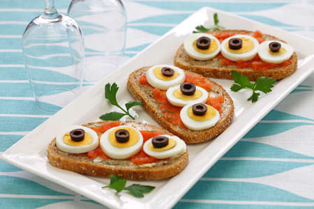 Swedish Open Sandwich with sliced boiled egg, black olives and dill on top of seasoned cod roe rye bread.