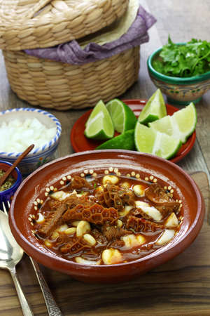 Menudo Rojo is a traditional mexican soup made with honeycomb tripe and hominy in broth with chile guajillo base.