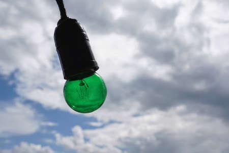 isolated: Green Edison light bulb isolated on beautiful cloudy sky Stock Photo