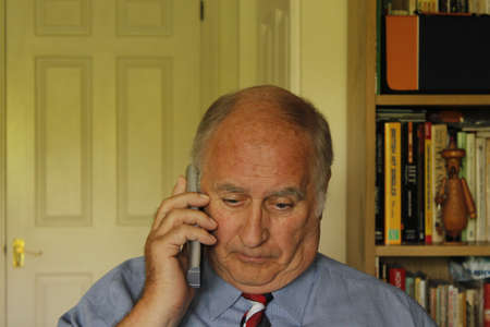 Man Reading document and talking on the telephone, photo