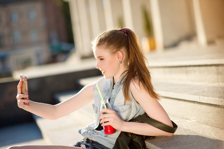 stylishly: A beautiful young stylishly dressed girl walks in the city, drinks juice or a cocktail, eats sweets, makes selfie on a mobile phone
