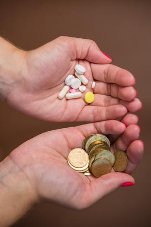 Pills and money in hand closeup Stock Photo