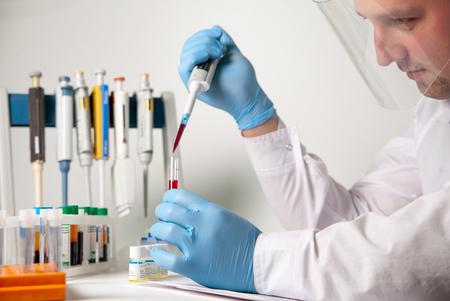 Wetenschappelijk laboratoriumtechnicus die met bloed en biomateriaal werkt via samplermeting en andere laboratoriumapparatuur in het laboratorium