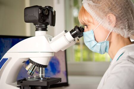 investigando: Laboratory assistant or technician in medical research lab looking into a microscope and doing research Foto de archivo