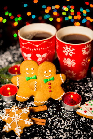 Christmas card - gingerbread man gingerbread, christmas decor, snow, candles, cup with cocoa, tea or coffee and Christmas light Stock Photo