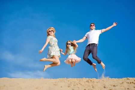 Beautiful happy family walking, running, jumping, having fun along the sand on the beach against the background blue sky in summer vacation