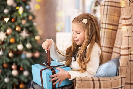 Girl, daughter, smiling, glad opens and receives gifts on Christmas Eve or New Year near Christmas tree Stock Photo