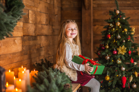 Girl, daughter, smiling, glad opens and  receives gifts on Christmas Eve or New Year near Christmas tree