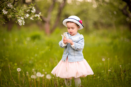 Little girl in a hat with a dandelion on a walk in a spring park or garden Stock fotó