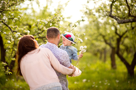 Family mom, dad and daughter are walking in the spring in a flowery garden, happy, laughing
