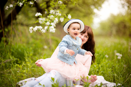 A little girl with her mother on a walk in the spring garden, socialize, laugh, embrace, rejoice, mother and daughter