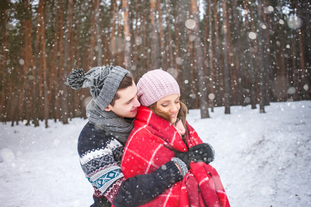 The guy embraces the girl and covers it with a warm blanket in the winter forest, couple of lovers