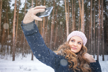Young woman taking picture with smartphone selfie stick on over winter background