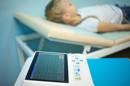 Electrocardiogram, cardiac cardiograph and conduct research in pediatrics, a girl doing an electrocardiogram