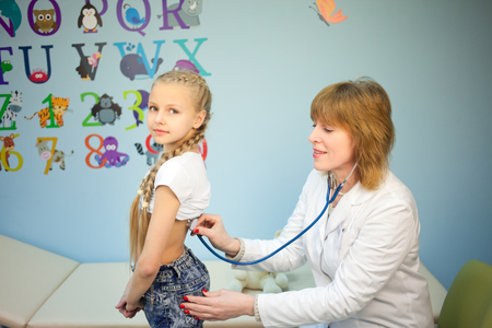Doctor pediatrician examines girl listening stethoscope, measure the temperature of the body and looks throat