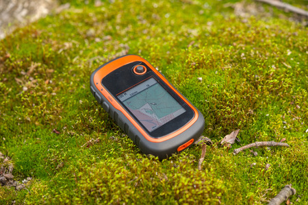 GPS device in the forest on a moss, outdoor, hiking, trekking