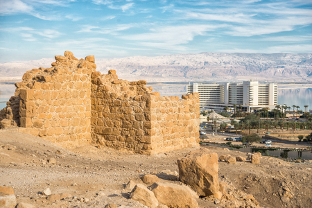 The ruins of the ancient city wall against the backdrop of the sea and the modern city