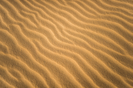 Waves of yellow sand closeup. Background, wallpaper, pattern or texture.