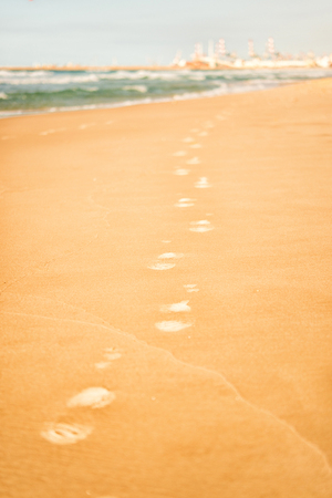 Footprints on the warm yellow sand near sea or ocean Banque d'images