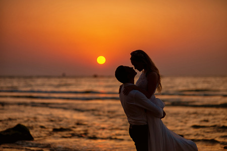 Bride and groom, newlyweds, honeymoon on the beach sunset sun Banque d'images