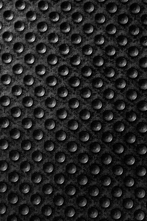 Black dotted texturised technological seamless fabric or surface closeup