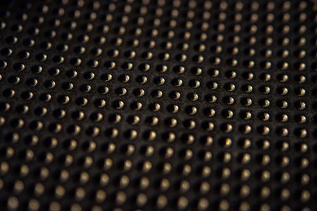 Black golden dotted texturised technological seamless fabric or surface closeup