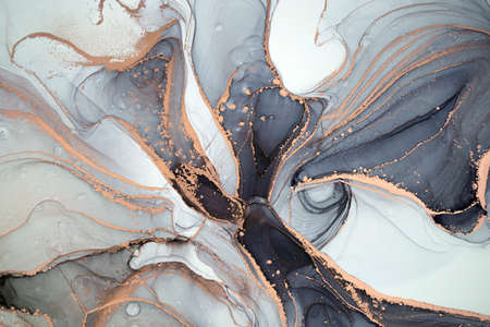 Luxury abstract fluid art painting in alcohol ink technique, mixture of black, gray and gold paints. Imitation of marble stone cut, glowing golden veins. Tender and dreamy design.