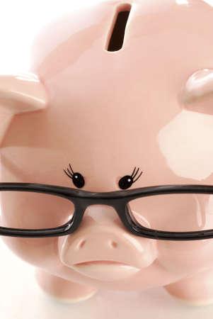 black rimmed: pink piggy bank with sad expression wearing black rimmed glasses on white background