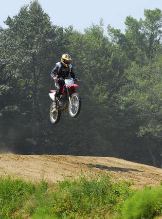 daredevil: teenage boy jumping hills on a dirt bike