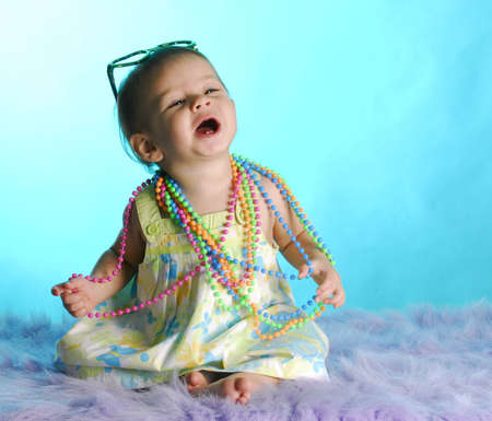 blue background: baby girl with two front teeth wearing colorful clothes on blue background