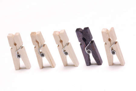 clothes pegs with one black one - concept of odd man in a group