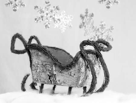 old fashioned winter sleigh with large snowflakes falling down in black and white photo