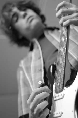 fourteen: fourteen year old teenage boy playing or practicing guitar Stock Photo